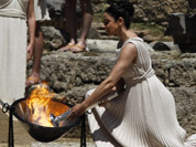 A high priestess, lights the Olympic flame using a concave mirror to concentrate the sun`s rays, in the final dress rehearsal for the lighting of the flame held in Ancient Olympia, Greece.