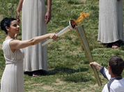 An actress as high priestess, passes on the Olympic flame to Spyros Gianniotis, a 32-year-old Liverpool-born swimmer, who won a silver medal for Greece in the 5-kilometer open water event four years ago in Beijing, during the lighting of the flame ceremony in Greece.