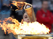 Actress Ino Menegaki, dressed as a high priestess, lights the torch at a ceremony in Panathinean stadium in Athens. The torch begins its 70-day journey to arrive at the opening ceremony of the London 2012 Olympics, from the Greek capital.