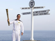 British Olympic sailing hero and three time gold medalist Ben Ainslie holds the Olympic torch at the official start of the London 2012 Olympic games torch relay at Land`s End, south west England.