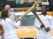 Will.i.am of the Black Eyed Peas passes the Olympic Flame to torchbearer Emma Fowler in Taunton, England.
