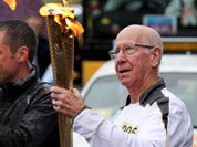 Bobby Charlton carrying the Olympic Flame on the Torch Relay leg between Salford and Moss Side in Manchester, England.