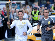 Torchbearer 140 Lord Sebastian Coe carries the Olympic Flame on the Torch Relay leg through Sheffield, England.