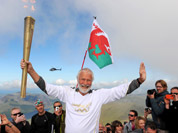 Sir Chris Bonington holding the Olympic Flame on the top of Mount Snowdon in Wales during the Olympic Torch Relay.