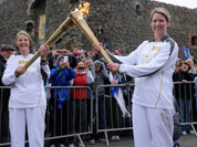 Kathleen Irvine, left, passes Lisa Hickson the Olympic Flame outside of Carrickfergus Castle in Carrickfergus Northern Ireland during the Olympic Torch Relay.
