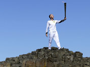 Peter Jack holds the Olympic torch aloft at the Giant`s Causeway in county Antrim, Northern Ireland.