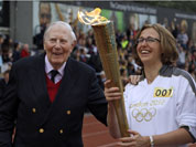 The Olympic Flame is passed between Sir Roger Bannister and Oxford doctoral student Nicola Byrom on the running track at Iffley Road Stadium in Oxford, England.