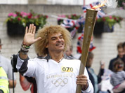 This image made available by LOCOG shows former Colombian soccer player Carlos Valderrama carrying the Olympic Flame on the Torch Relay leg between Slough and Windsor, England.