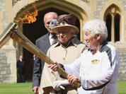 This image made available by LOCOG shows Queen Elizabeth II, second right, and the Duke of Edinburgh watching the Torch Kiss as Torchbearer 073 Gina Macgregor, right, passes the Olympic Flame to Torchbearer 074 Phillip Wells, left, outside Windsor Castle, Windsor, England.