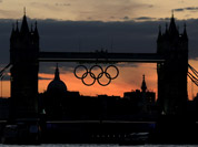 The Olympic rings hang from the Tower Bridge after sunset, as London prepares for the 2012 Summer Olympics.