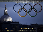 St. Paul`s Cathedral is seen in the distance as the Olympic rings hang from the Tower Bridge in London.