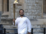 Torchbearer Abdul Kasam carries the Olympic torch at the Tower of London. The Opening Ceremony of the London Olympic Games is on Friday, July 27, 2012.