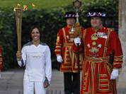 British retired champion Dame Kelly Holmes pose for the photographers with the Olympic flame at the Tower of London.