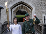 British retired champion Dame Kelly Holmes, left, poses for the photographers with the Olympic flame, along with British Royal Marine Martyn Williams, 23, right, who abseiled from a Sea King helicopter, with the lantern with the Olympic flame strapped to his body, at the Tower of London.