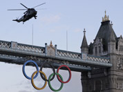 A British Royal Marine Sea King helicopter carrying the Olympic flame flies past the Tower Bridge in London, as it arrives to the Tower of London.
