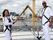The photo provided by LOCOG shows torchbearers Nadia Comaneci, left, and John Amaechi as they handing over the light of the Olympic Torch on the viewing platform of the North Greenwich Arena, London.