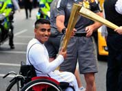 Photo provided by LOCOG, singer Paloma Faith passes the Olympic Flame to torchbearer Sheikh Sheikh on the Torch Relay leg through London.