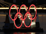 A set of Olympic Rings float on a barge in the River Thames off of Battersea park in London. 