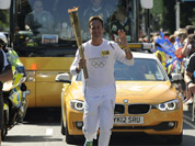 In this photo provided by LOCOG, torchbearer and former cricket captain Michael Vaughan carries the Olympic Flame on the Torch Relay leg through Hillingdon, England.
