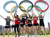 Basketball team members from Canada jump in the air in front of the Olympic rings inside the London 2012 Olympic Village in Stratford.