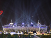 Searchlights shine over the Olympic Stadium during a rehearsal for the opening ceremony at the 2012 Summer Olympics in London.