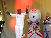 In this photo provided by LOCOG, torchbearer 153 Daley Thompson acknowledges the crowd after lighting the cauldron at the end of Day 68 in the Torch Relay in London.