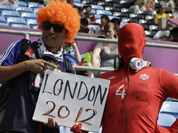 A Canadian masked fan and Japan fan, posing for a picture during the group F soccer match between Japan and Canada at the London 2012 Summer Olympics.