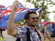 Zaki Abdullah carries a New Zealand flag as he walks into the Olympic Park before the Opening Ceremony for the 2012 Summer Olympics in London.