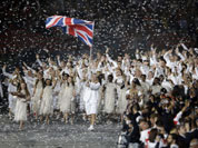 Great Britain`s Chris Hoy carries the national flag as confetti surrounds the team during the Opening Ceremony at the 2012 Summer Olympics in London.