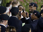 Professional basketball player LeBron James takes pictures with members of the the United States` Olympic team during the Opening Ceremony at the 2012 Summer Olympics in London.