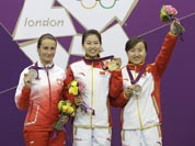 China`s Yi Siling, center, celebrates winning the gold medal in the women`s 10-meter air rifle event, alongside silver medalist Poland`s Sylwia Bogacka, left, and bronze medalist China`s Yu Dan, right, at the 2012 Summer Olympics.