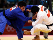 Hiroaki Hiraoka of Japan competes against Ashley McKenzie of Great Britain (in blue) during the elimination round of the men`s 60kg judo competition at the 2012 Summer Olympics.
