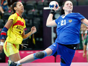 Victoria Zhilinskayte of Russia, center, takes a shot at goal as Angola`s Nair Almeida, left, and Natalia Bernardo, right, watch during their women`s handball preliminary match at the 2012 Summer Olympics.