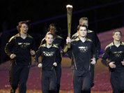 Torchbearers run during the Opening Ceremony at the 2012 Summer Olympics in London.