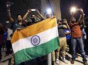 Men hold the national flag of India as they take photographs of fireworks from a neighborhood outside the Olympic Park during the 2012 Summer Olympics Opening Ceremony in London.