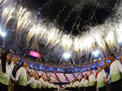 Athletes and volunteers watch a fireworks display after the Olympic cauldron was lit during the Opening Ceremony at the 2012 Summer Olympics in London.