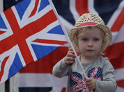 A young girl shows her support for the Great Britain team at a park screening a live telecast of the opening ceremony of the 2012 Summer Olympics in London.