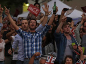 Visitors at a park celebrate during the live telecast of the Opening Ceremony of the 2012 Summer Olympics in London.