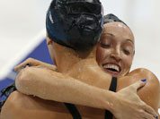 United States` Claire Donahue, right, embraces United States` Dana Vollmer after competing in the women`s 100-meter butterfly swimming semifinal at the Aquatics Centre in the Olympic Park during the 2012 Summer Olympics in London.