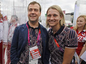 Russian Prime Minister Dmitry Medvedev center, poses with Russian Olympics team members during his visits to Olympic village at the 2012 Summer Olympics, in London.