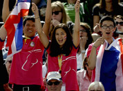 Fans cheer as Nina Lamsan Ligon, of Thailand, and her horse Butts Leon, compete in the equestrian eventing dressage phase at the 2012 Summer Olympics in London. 