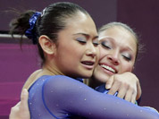 Brazilian gymnast Ethiene Cristina Gonser Franco, right, hugs teammate Harumy Mariko de Freitas, left, during the artistic gymnastics women`s qualification at the 2012 Summer Olympics in London.