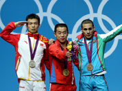North Korea`s Om Yun Chol, center, celebrates winning the gold with China`s silver medal winner Wu Jingbiao, left, and Azerbaijan`s bronze medal winner Valentin Hristov in the men`s 56kg weightlifting competition at the 2012 Summer Olympics.