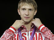 Russia`s Nikolay Kovalev stands on the medal stand after winning the bronze medal match against Romania`s Rares Dumitrescu in the men`s fencing individual sabre at the 2012 Summer Olympics.