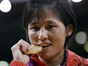 North Korea`s An Kum Ae, of North Korea, bites her gold medal from the women`s 52-kg judo competition at the 2012 Summer Olympics.