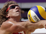 Aleksandrs Samoilovs of Latvia sets the ball during a beach volleyball match against the Republic of South Africa at the 2012 Summer Olympics in London.