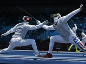 Radu Daraban of Romania, left, and Valerio Aspromonte of Italy compete during his men`s individual foil fencing match against Mohamed Samandi of Tunisia at the 2012 Summer Olympics.