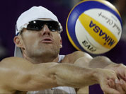 Jacob Gibb of the United States sets the ball during a loss to Poland during a beach volleyball match at the 2012 Summer Olympics in London.