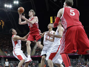 Russia`s Andrei Kirilenko (15) shoots between China`s Wang Zhizhi, left, and China`s Yi Jianlian, right, during the first half of a preliminary en`s basketball game at the 2012 Summer Olympics in London.