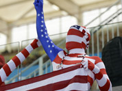 Fans dressed in costumes in the colors of the U S flag watch swimming competitions at the Aquatics Centre in the Olympic Park during the 2012 Summer Olympics in London.